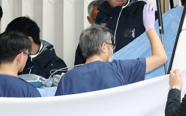 転院先の京都市内の病院に搬送される青葉真司容疑者(14日午前)=一部画像処理しています