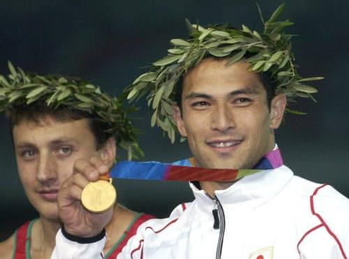 アテネ五輪の男子ハンマー投げで繰り上がり優勝、授与された金メダルを手に笑顔の室伏。左は銀のイワン・チホン=共同