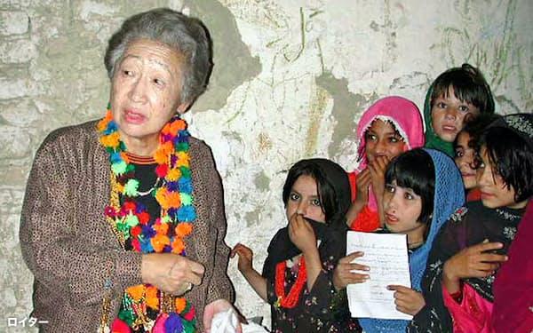 2000年9月、パキスタンのアフガニスタン難民キャンプで、子供たちから手作りのハンカチを受け取る緒方貞子国連難民高等弁務官=ロイター