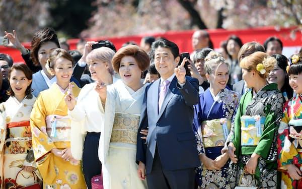 「桜を見る会」で参加者とポーズをとり、写真に納まる安倍首相(4月13日、東京・新宿御苑)