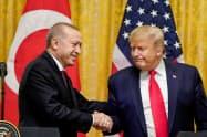13日、共同記者会見の席で握手するトランプ大統領(右)とエルドアン大統領(ワシントン)=ロイター