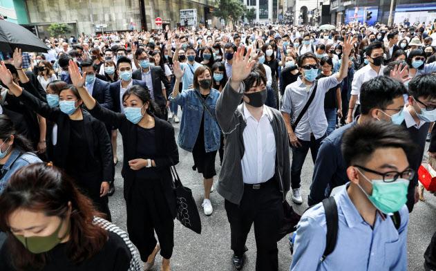 14日昼、金融街の中環で政府に抗議する市民=ロイター