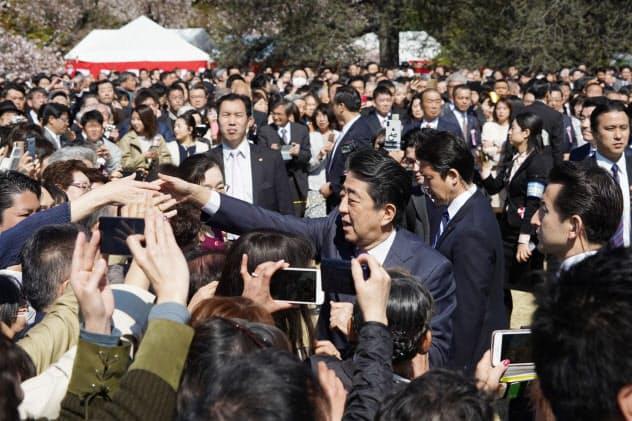 「桜を見る会」の来場者と握手する安倍首相(4月、東京・新宿御苑)