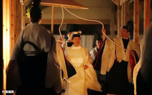 薄明かりの中、「悠紀殿供饌の儀」のため、祭服を着て悠紀殿に向かう天皇陛下(14日、皇居・東御苑)=代表撮影
