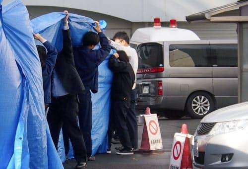 青森県八戸市で女子児童が切り付けられた事件で、送検のため青森県警八戸署を出る男子生徒を乗せた車(右)(14日午前9時36分)=共同
