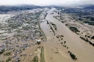 台風19号による大雨で千曲川の堤防(中央左)が決壊した(10月13日、長野市)=共同