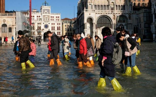 浸水したサンマルコ広場を歩く観光客(14日)=ロイター