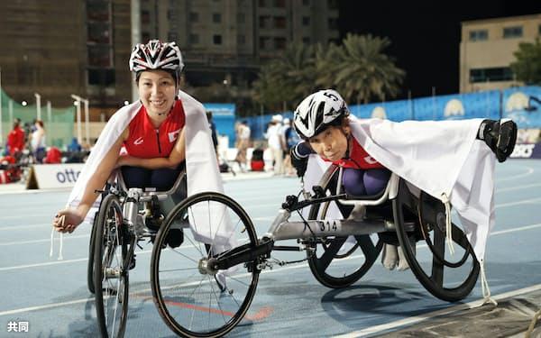 女子100メートル(車いす)で、東京パラリンピック代表の内定条件をクリアし、笑顔の木山(左)と田中=共同