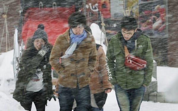 激しい風雪の中を歩く人たち(2016年3月、北海道小樽市)=共同