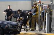14日、銃乱射事件が起きた米サンタクラリタの高校で、けが人を搬送する救急隊員(DavidCrane/The Orange County Register提供)=AP