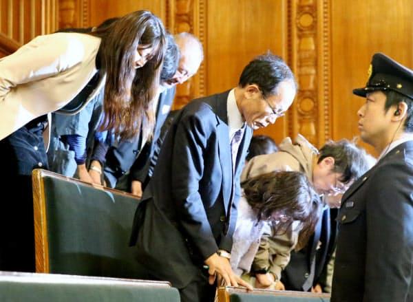 参院本会議でハンセン病家族補償法が成立し、立ち上がって一礼する原告ら(15日)