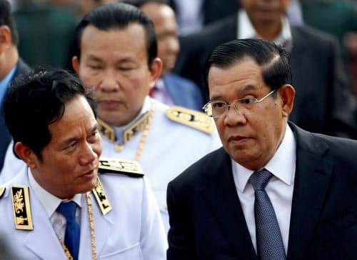 フン・セン首相(右)は制裁回避に向け動き始めている(10日、プノンペン)=ロイター