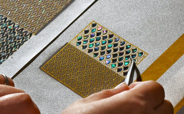 薄く削り出した貝殻の真珠層を和紙に貼り付ける=小幡真帆撮影