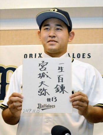 オリックスへの入団が決まり、「一生百錬」と記した色紙を掲げる沖縄・興南高の宮城大弥投手(15日、那覇市)=共同