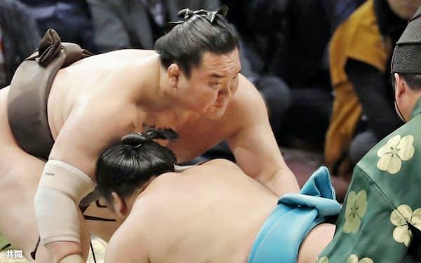 白鵬(左)が上手出し投げで明生を下す(15日、福岡国際センター)=共同