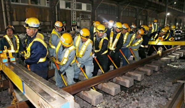 高輪ゲートウェイ駅に線路を通すための切り替え工事で、バールを使い線路を動かす作業員ら(16日未明、東京都港区)=代表撮影