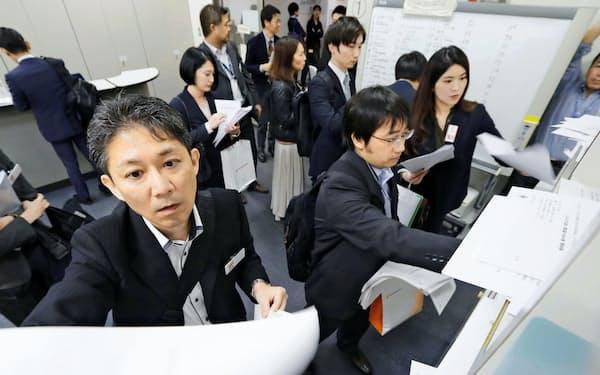 決算資料を投函(とうかん)する企業の担当者ら(8日、東証)