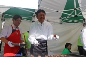 牛串焼きを調理する東京電力ホールディングスの小早川智明社長(中央、16日、東京都内)