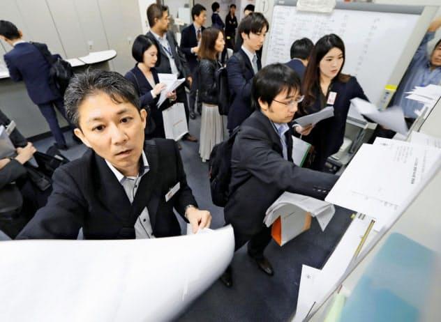 上場企業の4~9月期決算は減益に(東証で資料を投かんする企業の担当者ら、8日)