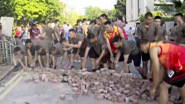 16日、香港の大学で、デモ隊がばらまいたれんがを拾う中国人民解放軍の軍人(AP=共同)