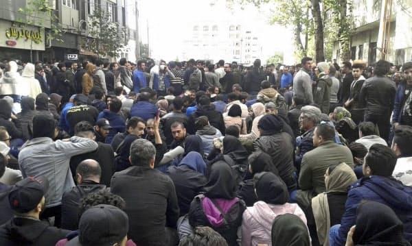 16日、イラン北部の都市サリでガソリン値上げに抗議する人々=AP