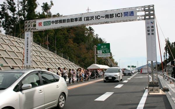 新たに開通した区間の通り初めで富沢ICを出発する車両(17日)