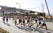 第9回神戸マラソンで、明石海峡大橋のそばを走るランナー(17日、神戸市)=共同