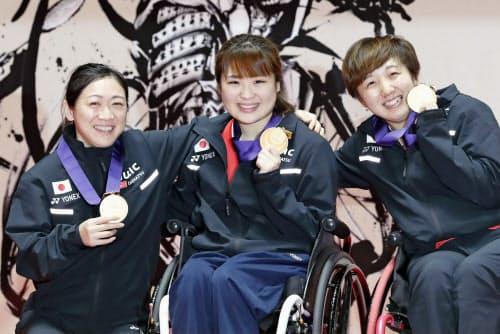 メダルを手に笑顔を見せる、女子シングルス(上肢障害)で優勝した鈴木亜弥子(左)と女子ダブルス(車いす)で優勝した里見(中央)、山崎組(17日、国立代々木競技場)=共同
