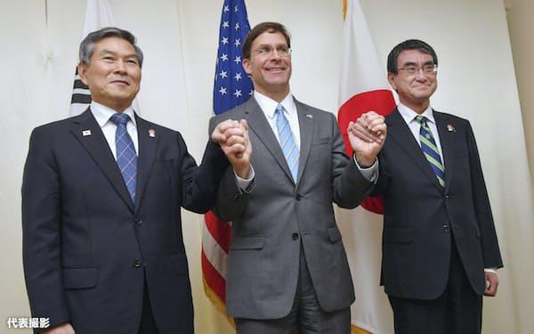日米韓防衛相会談を前に手をつなぐ(左から)韓国の鄭景斗国防相、エスパー米国防長官、河野防衛相(17日午後、バンコク)=代表撮影