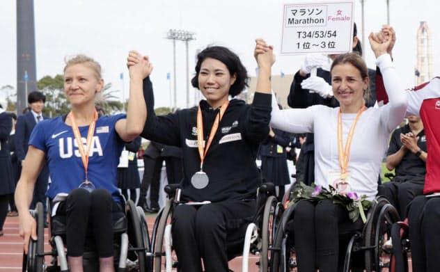 表彰式で笑顔を見せる、女子で日本新記録をマークし2位の喜納翼(中央)。右は世界新記録で優勝したマニュエラ・シャー(17日、大分市営陸上競技場)=共同
