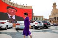 中国政府は少数民族ウイグル族への監視や強制収容を進めてきた(2018年、巨大スクリーンに習近平国家主席の映像が映し出された新疆ウイグル自治区)=ロイター