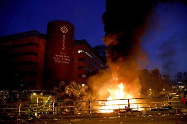 炎が上がる香港理工大周辺(18日)=ロイター