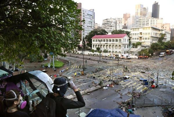 香港理工大で周囲を警戒する若者たち(18日)=共同