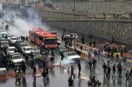 交通を妨害し、ガソリン価格の引き上げに抗議する市民ら(16日、テヘラン)=WANA・ロイター