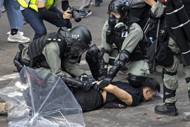 18日、重装備の警察官がデモ参加者を拘束した=AP