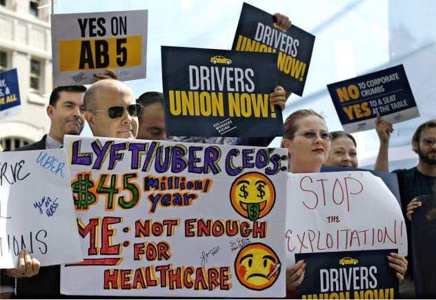 米カリフォルニア州ではインターネットを介して仕事を請け負う個人らを従業員として扱うよう企業に促す新法が成立した(写真は新法成立を求めていた活動家ら)=AP