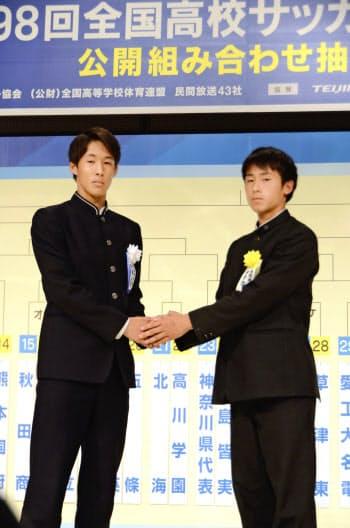 全国高校サッカー選手権で対戦が決まり、握手する青森山田の武田主将(左)と米子北の田中主将(18日、東京都内)=共同