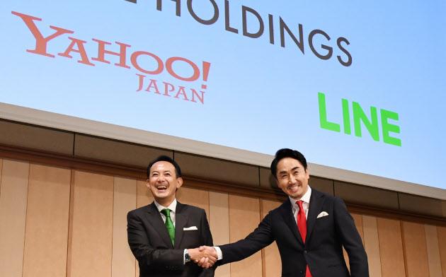 経営統合の記者会見で握手するZホールディングスの川辺健太郎社長(左)とLINEの出沢剛社長(18日、東京都港区)