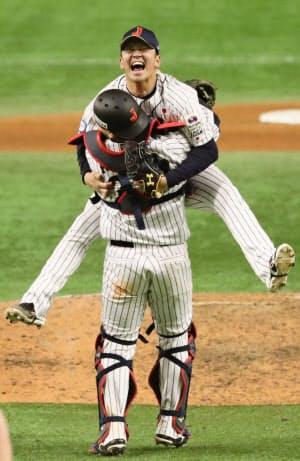 「プレミア12」で初優勝を果たし、捕手会沢と抱き合う山崎=共同