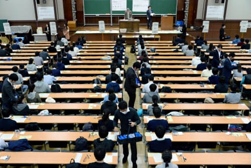 大学入試センター試験で、受験生にリスニング用の機器を配布する担当者(1月19日、東京都文京区の東京大学)