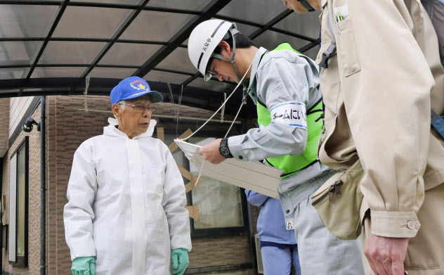 福島県郡山市で罹災証明書の調査に訪れた県外の自治体職員(中)ら(10月24日)=共同