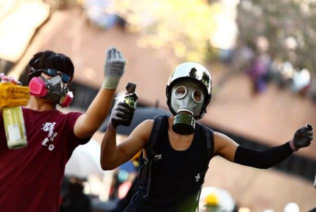 デモ参加者の多くがマスクや覆面で顔を隠している(17日、香港)=ロイター