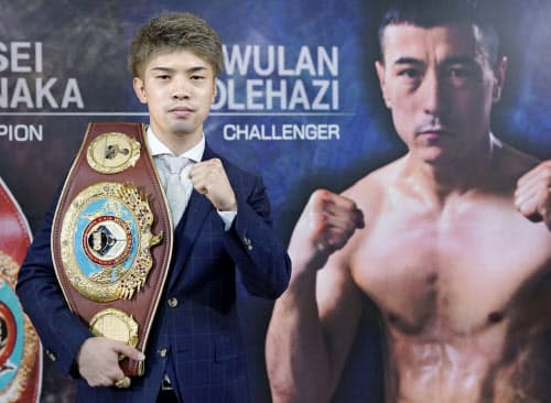 挑戦者ウラン・トロハツのパネルの前で写真撮影に応じる、WBO世界フライ級王者の田中恒成(19日、名古屋市)=共同