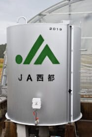 KDDIなどが開発したシステムを利用する農家のビニールハウスの燃料タンクと、タンクに設置された圧力センサー(宮崎県西都市)