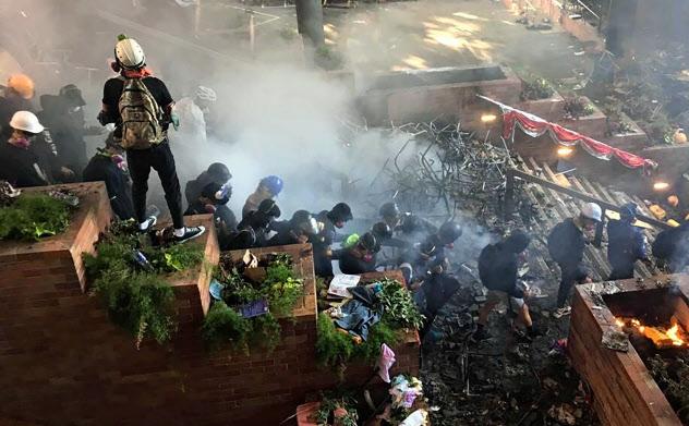 18日、香港理工大学からの退去を試みるデモ隊=AP