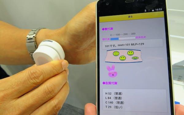 京セラの「糖質ダイエットモニタ」は手首にセンサーを押し当てて糖の代謝を調べる