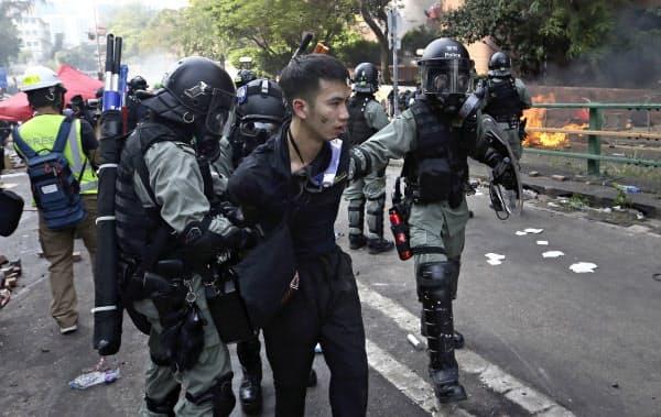 香港理工大学付近で拘束されるデモ隊の男性(18日)=AP
