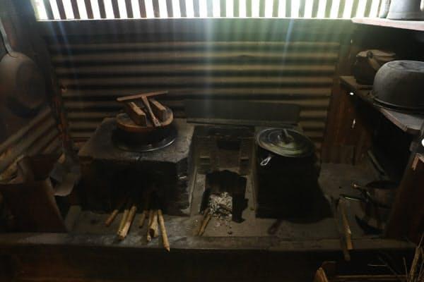 日本から持ち込んだ羽釜があるかまど。まきにはコーヒーの木が使われた