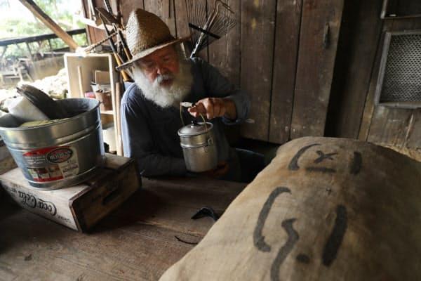 100年前のコーヒー農園労働者のいでたちのジム・ミラーさん。弁当箱も当時のもの