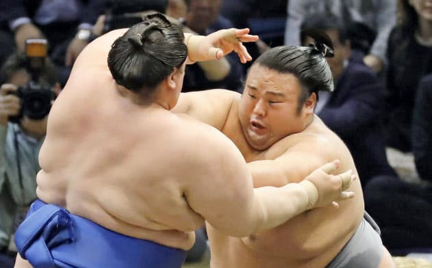 碧山(左)を押し出す貴景勝(20日、福岡国際センター)=共同